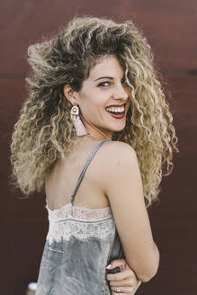 Portrait of laughing young woman with dyed blond ringlets - DAMF00140