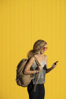 Laughing young woman with  backpack looking at cell phone in front of yellow background - DAMF00143