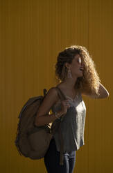 Laughing young woman with backpack in front of yellow background - DAMF00146