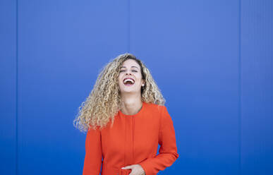 Portrait of laughing young woman wearing red dress in front of blue background - DAMF00149
