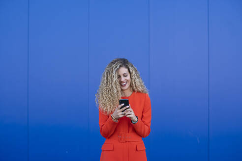 Portrait of young woman wearing red dress using cell phone in front of blue background - DAMF00152