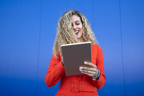 Portrait of young woman wearing red dress in front of blue background using digital tablet - DAMF00155