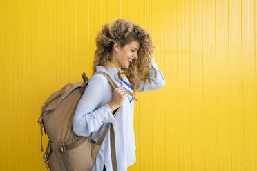 Laughing young woman carrying backpack in front of yellow background - DAMF00161