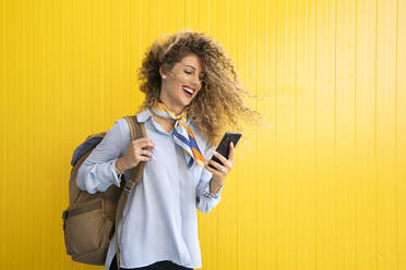 Laughing young woman with backpack in front of yellow background looking at cell phone - DAMF00164
