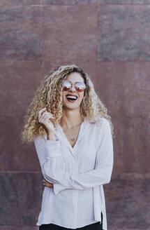Portrait of laughing young woman wearing sunglasses - DAMF00167