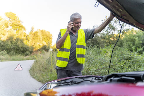 Senior man standing at his broken car wearing a safety vest and using his smartphone - AFVF04056