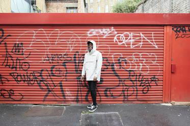 Laughing man wearing rainjacket standing in front of graffiti on roller shutter - IGG01365