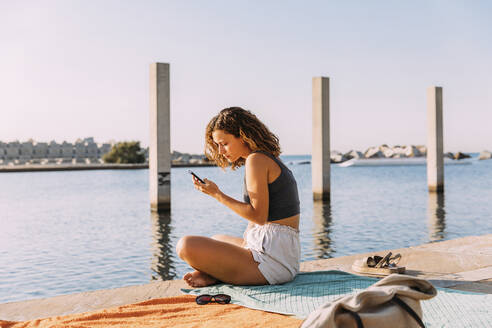 Young woman sitting on a pier at the sea using smartphone - MOSF00047