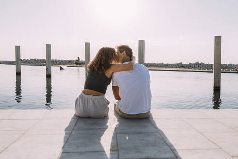 Rear view of young couple sitting on a pier at the sea kissing - MOSF00062