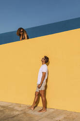 Young man looking at woman behind a yellow wall - MOSF00068
