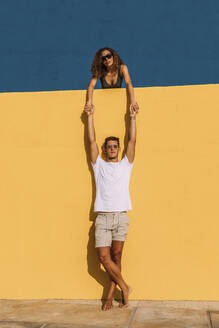 Young man and woman behind a yellow wall holding hands - MOSF00071