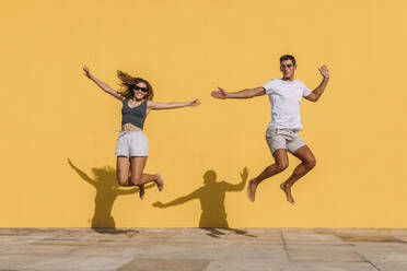 Young couple jumping in front of a yellow wall - MOSF00074