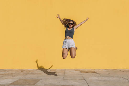 Happy young woman jumping in front of a yellow wall - MOSF00077