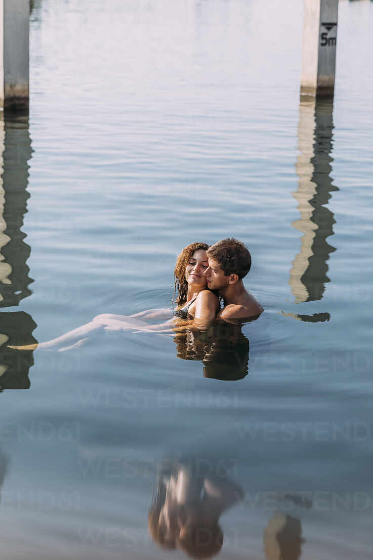 Affectionate young couple bathing in the sea - MOSF00086 - Marcos Osorio/Westend61