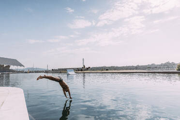 Young man jumping into water from a pier - MOSF00089