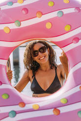 Portrait of happy young woman behind inflatable float in donut shape - MOSF00095