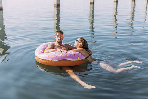 Young couple bathing in the sea on inflatable float in donut shape - MOSF00098
