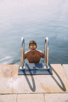Portrait of young man wearing sunglasses getting out of the water - MOSF00101
