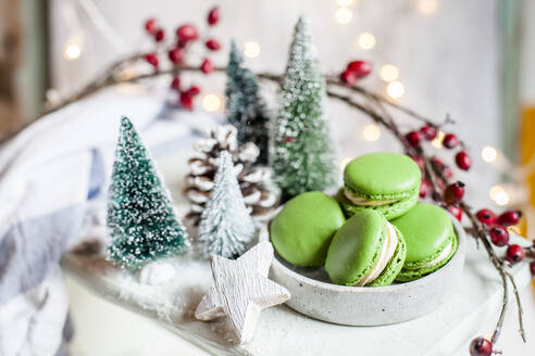 Bowl of green macaroons and Christmas decorations - SBDF04030
