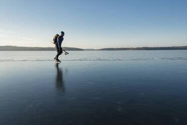 Man ice-skating on frozen lake - JOHF03024