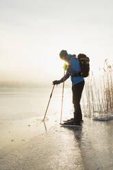 Man ice-skating on frozen lake - JOHF03030