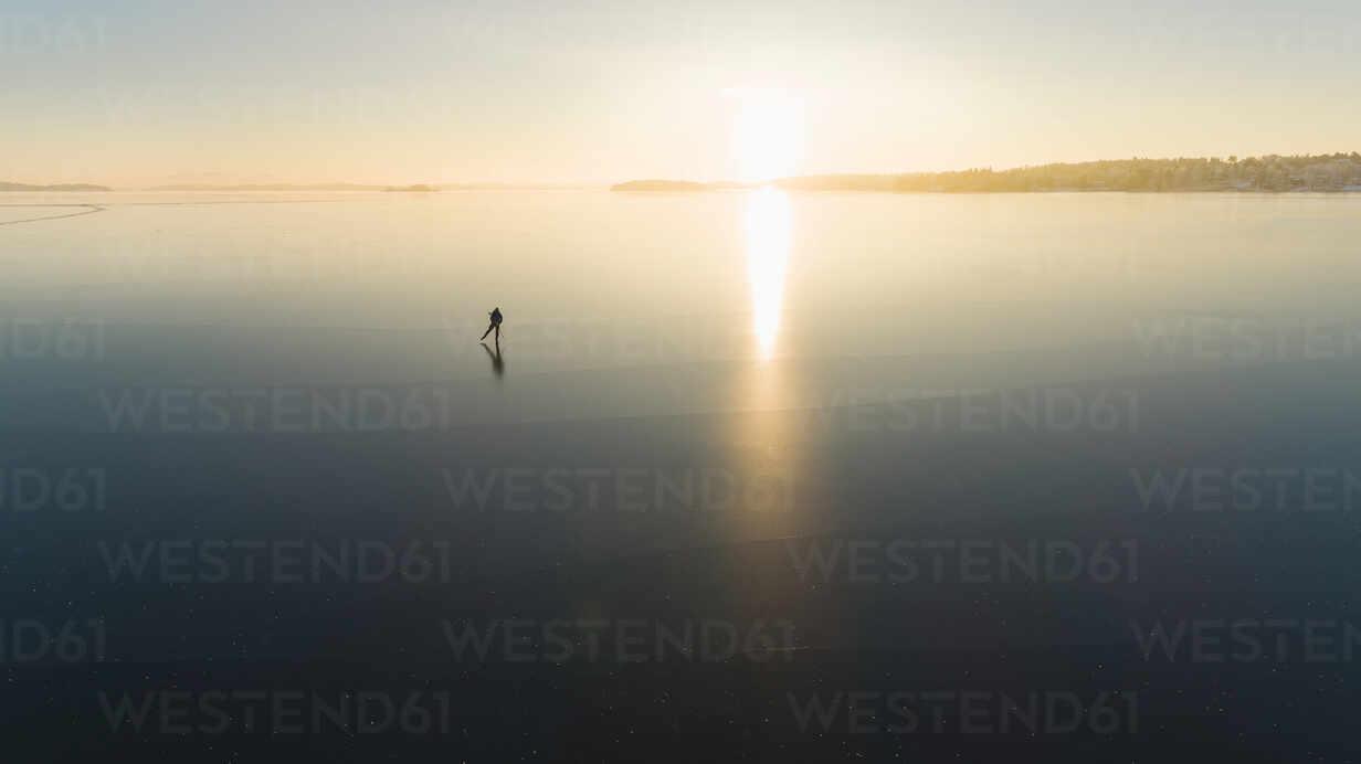 Ice skater on frozen sea - JOHF03033 - Johner Images/Westend61