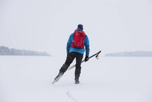 Man ice-skating on frozen lake - JOHF03042