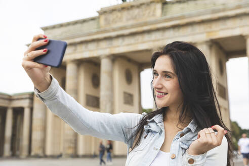 Happy young woman taking a selfie at Brandenburg Gate, Berlin, Germany - WPEF02038