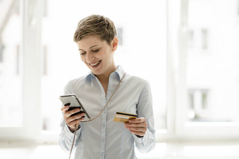 Happy woman using cell phone and credit card - KNSF06738