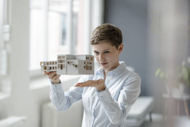 Confident businesswoman holding architectural model in office - KNSF06741