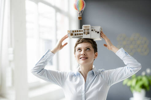 Smiling businesswoman carrying architectural model on her head with hot-air balloon floating above - KNSF06744