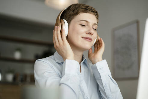 Portrait of businesswoman listening to music with headphones - KNSF06750