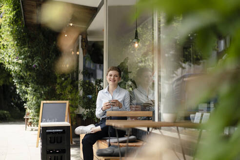 Portrait of smiling businesswoman at a cafe - KNSF06759