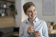 Happy businesswoman in a cafe holding a mug - KNSF06783