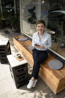 Portrait of a happy businesswoman at a cafe - KNSF06789
