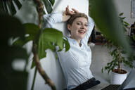 Portrait of a businesswoman with laptop sitting on the floor surrounded by plants - KNSF06798