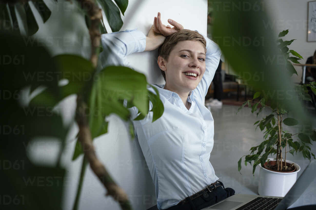 Portrait of a businesswoman with laptop sitting on the floor surrounded by plants - KNSF06798 - Kniel Synnatzschke/Westend61