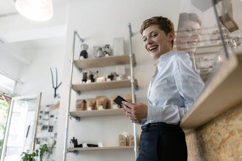Portrait of happy businesswoman with cell phone in a cafe - KNSF06801