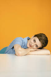 Portrait of woman resting on table with orange background - KNSF06810