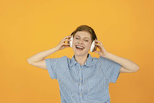 Portrait of happy woman listening to music with orange background - KNSF06813