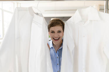 Portrait of happy businesswoman between two white shirts - KNSF06819