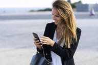 Smiling businesswoman with smartphone and earphones outdoors - GIOF07181