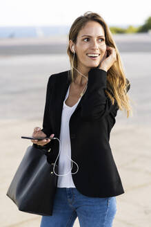 Happy businesswoman with smartphone and earphones outdoors - GIOF07184