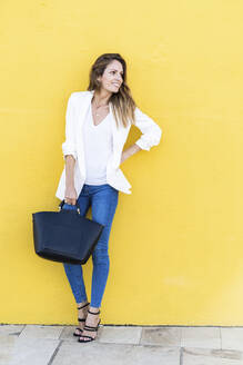 Smiling woman standing at a yellow wall holding a handbag - GIOF07208