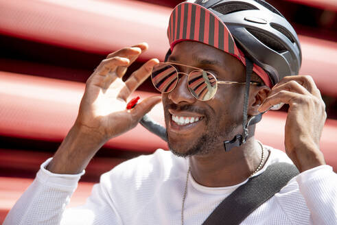 Smiling young man putting on his cycling helmet - CJMF00147