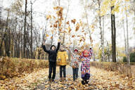 Group of four kids playing with autumn leaves - EYAF00562
