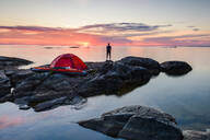 Man standing by tent at dusk - JOHF03810