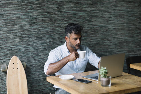 Casual businessman with skateboard using laptop in a cafe - ALBF01164