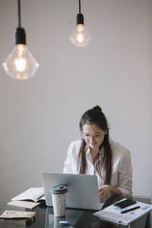 Young woman working at table in office using laptop - ALBF01182