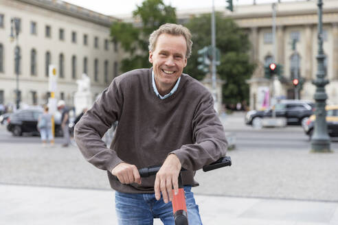 Portrait of happy senior man leaning on electric scooter in the city, Berlin, Germany - WPEF02052
